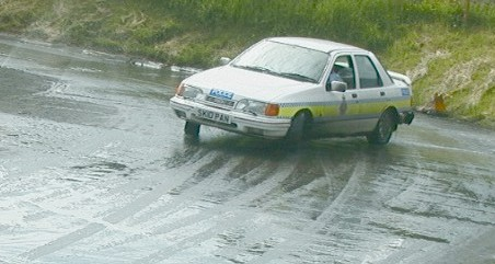 Some British police forces use old patrol cars, for skid training, with near-bald tyres inflated to very high pressures, running on concrete which is repeatedly coated with old oil then sprayed (see above) with fine jets of water. The resultant surface is hard even to walk on. Other UK forces now use cradles (see below) which can lift one or more of the car wheels far enough to lose traction, thereby creating whatever skid effects the instructor requires.